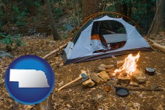 nebraska map icon and camping tent at a wilderness campsite